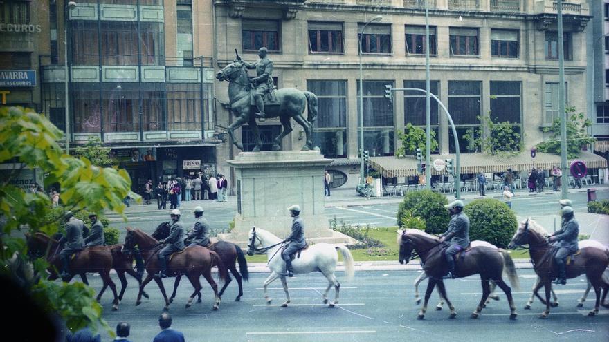 Policía a caballo franquistas patrullan por la Plaza del Ayuntamiento de Valencia frente a la antigua estatua de Franco.