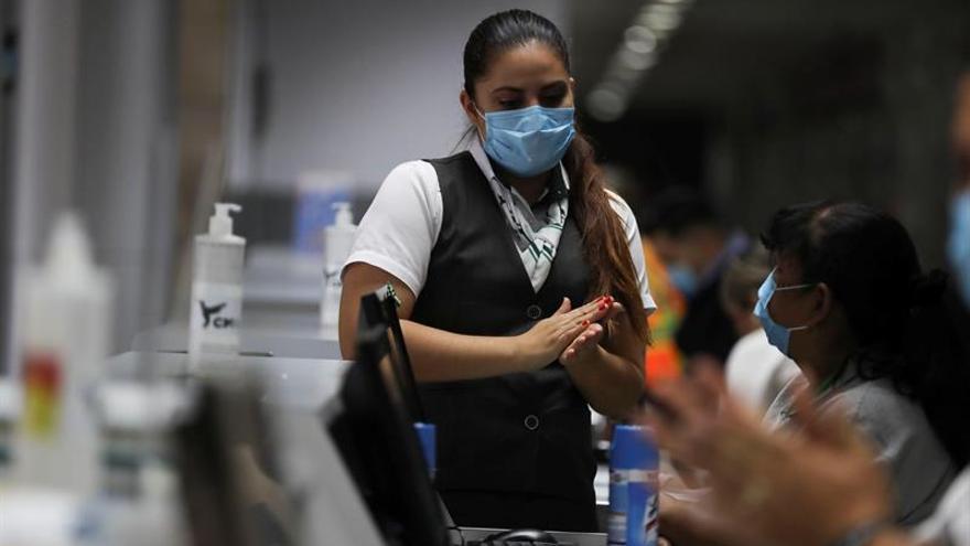 Empleados de líneas aéreas que funcionan en las instalaciones del Aeropuerto Internacional Toncontín se protegen con mascarillas el pasado miércoles en Tegucigalpa.