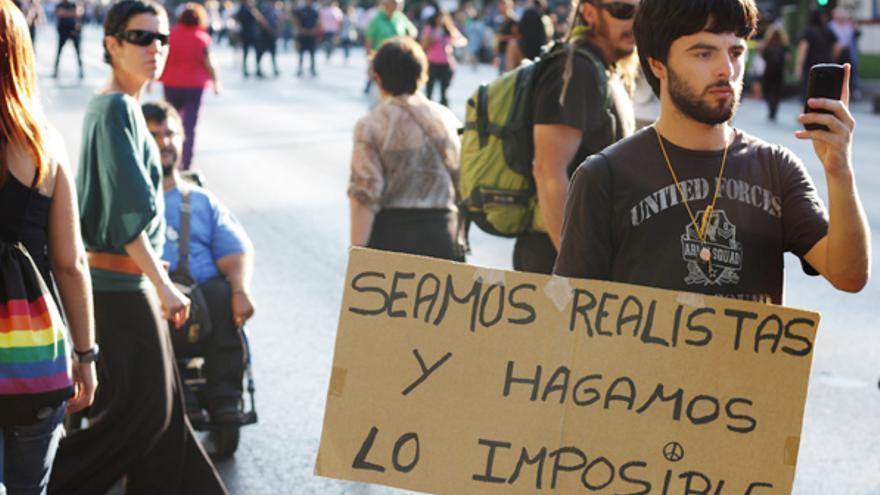 Pancarta, manifestante y móvil (Juan Luis Sánchez)