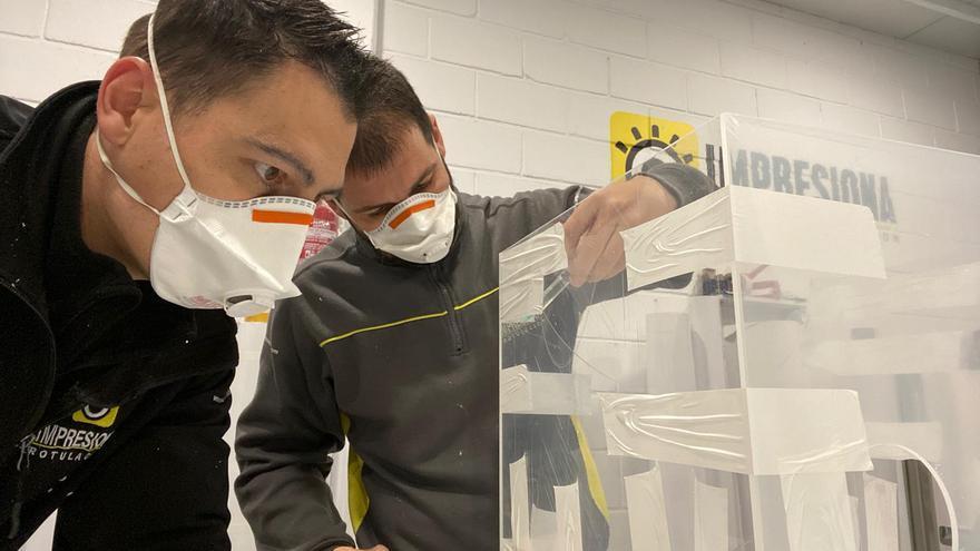 Investigadores trabajando en una caja para facilitar los trabajos de intubación de pacientes con COVID-19