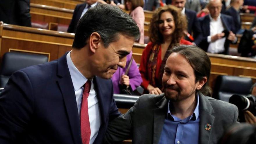 Pedro Sánchez y Pablo Iglesias en el Congreso de los Diputados, con la portavoz del Gobierno progresista, María Jesús Montero, de fondo.