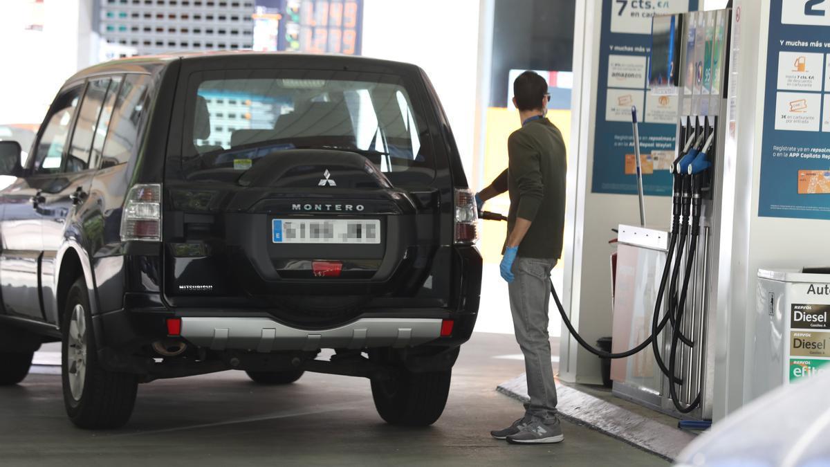 Un hombre echa gasolina a su coche.