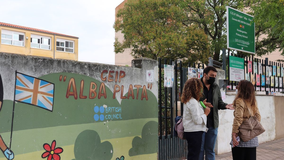 Tres personas conversan en la puerta del CEIP Alba Plata de Cáceres