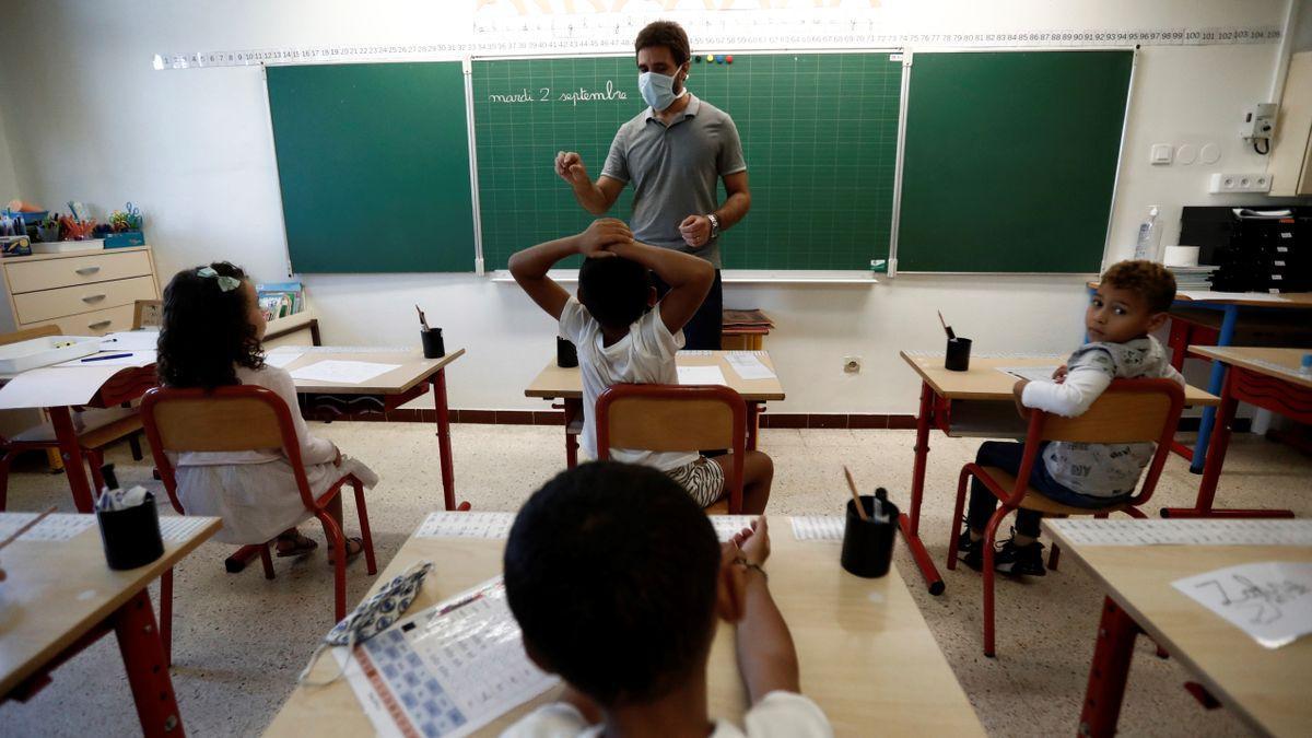 Imagen de archivo de un profesor con mascarilla dando clase a un grupo de alumnos de Infantil