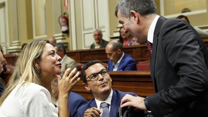 El presidente del Gobierno de Canarias, Fernando Clavijo (d), conversa con la portavoz del grupo socialista Dolores Corujo antes de comenzar el pleno del Parlamento regional