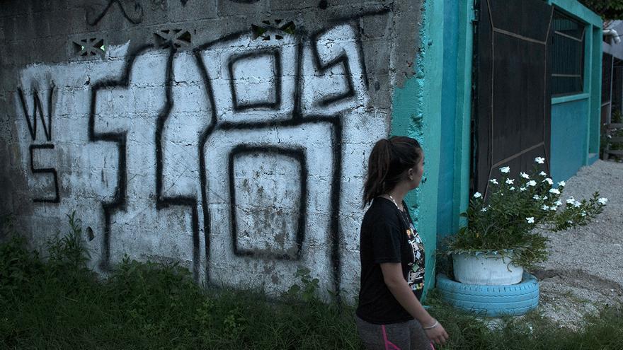 Até camina frente a uno de los placazos, grafitis en el argot pandillero, de la pandilla Barrio 18 en Cerrito Lindo, uno de los barrios dominados por esta pandilla en la Rivera Hernández, San Pedro Sula.