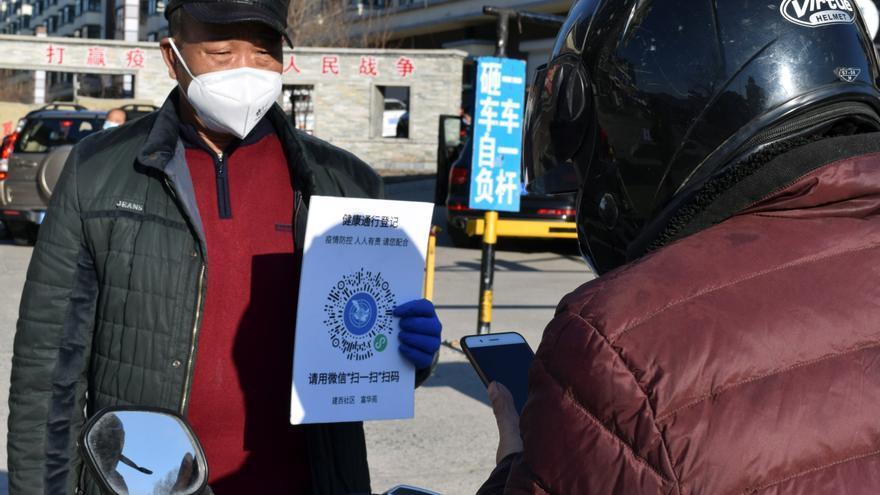 Un voluntario sostiene un cartel con un código QR para indicar el estado de salud en una entrada a un complejo residencial en Suifenhe © REUTERS / Huizhong Wu