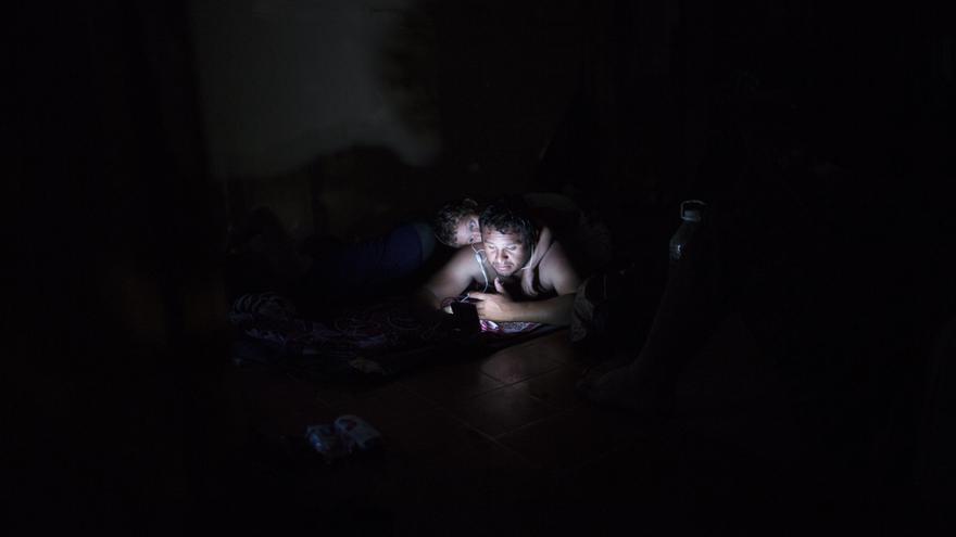 Un migrante centroamericano llamado Enrique mira las noticias de Honduras en su teléfono móvil, con su hijo Ian a sus espaldas, mientras descansan en un hotel abandonado en Matias Romero, estado de Oaxaca, México, el jueves 1 de noviembre de 2018. Miles de migrantes llegaron al pueblo de Matías Romero después de una agotadora caminata de 65 kilómetros desde Juchitán, Oaxaca, donde no consiguieron el transporte en autobús que esperaban. Foto: AP/Rodrigo Abd)