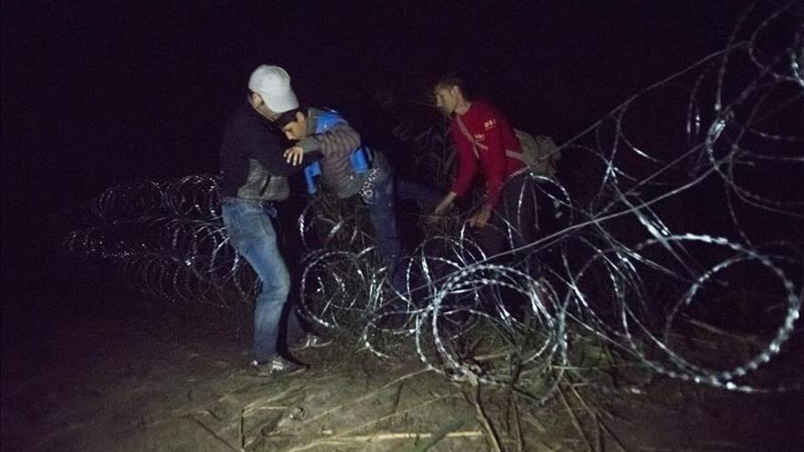 Inmigrantes cruzan la alambrada en la frontera entre Hungría y Serbia cerca de Roszke (Hungría) el 26 de agosto.