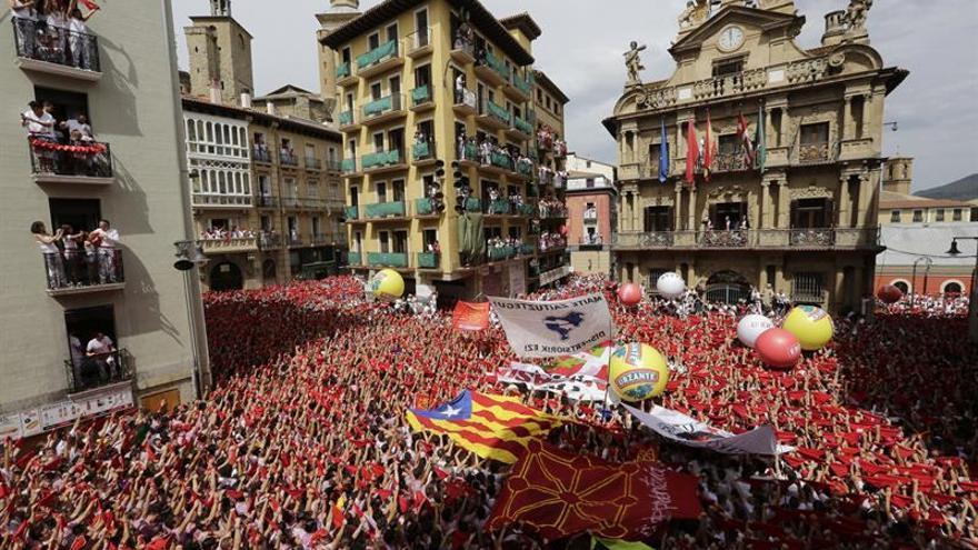 Miles de personas festejan con sus pañuelos rojos alzados el inicio de las fiestas de San Fermín 2017, tras el lanzamiento del tradicional chupinazo desde el balcón del Ayuntamiento de Pamplona.