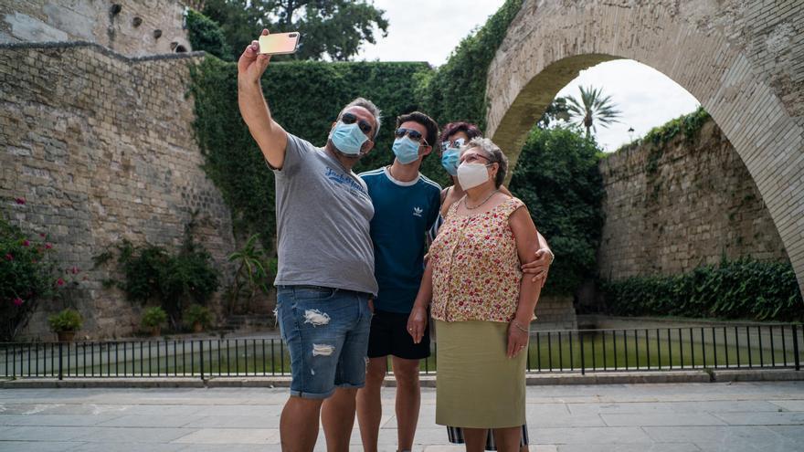 Varios turistas se hacen una foto junto a los Jardines de S'Hort del Rei de Palma de Mallorca