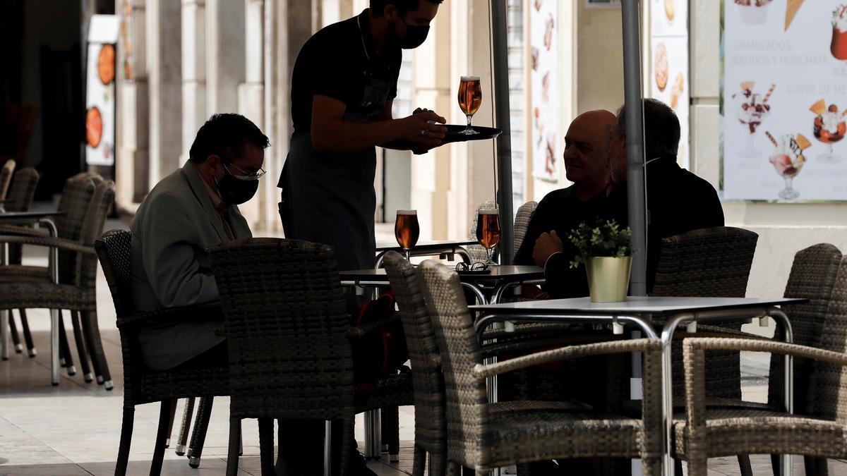 Un camarero atiende una mesa en una terraza del centro de Valencia.