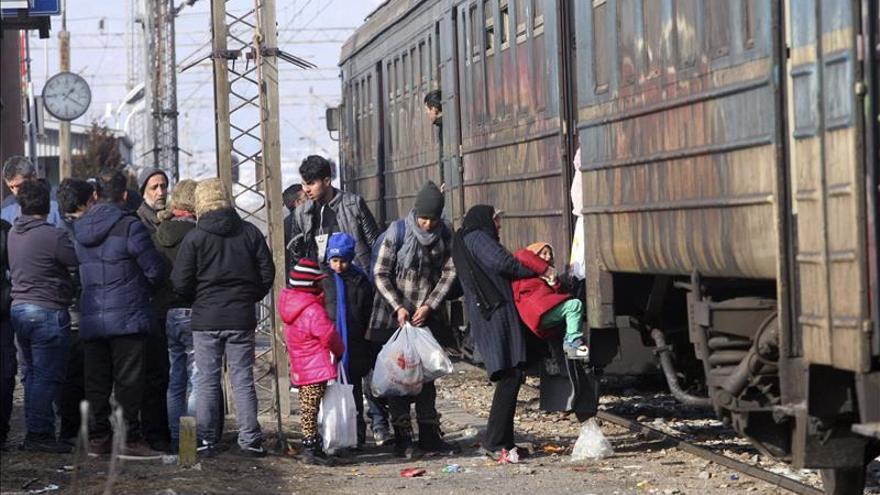 Un grupo de refugiados con sus pertenencias, junto a un tren.