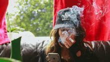 Una mujer fuma mientras consulta su teléfono móvil