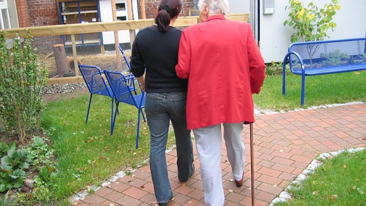 Imagen de archivo de una trabajadora del hogar y de cuidados paseando con una persona mayor.