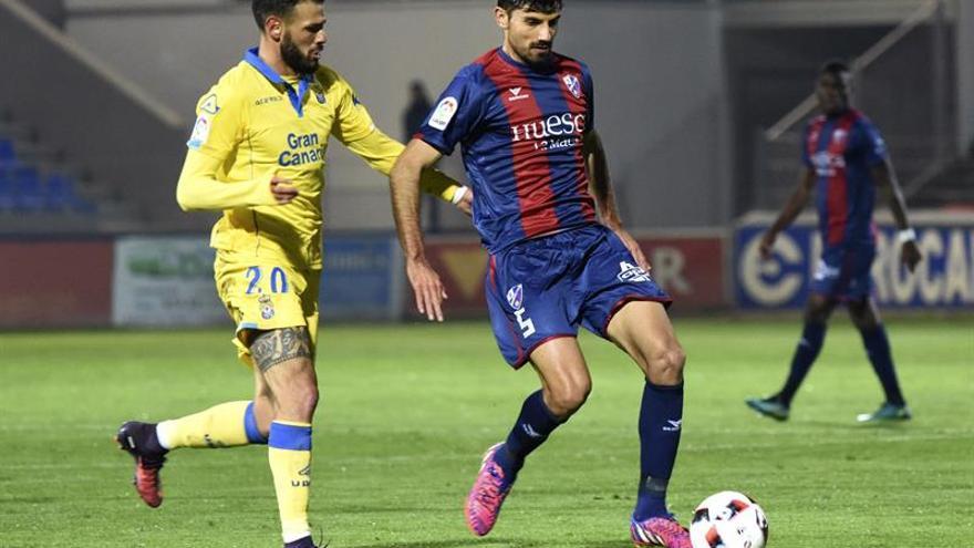 El centrocampista del Huesca Juan Aguilera (d) disputa un balón con el delantero Tyronne del Pino (i), de Las Palmas, durante el partido frente de ida de dieciseisavos de final de la Copa del Rey en El Alcoraz, de Huesca. EFE/Javier Blasco