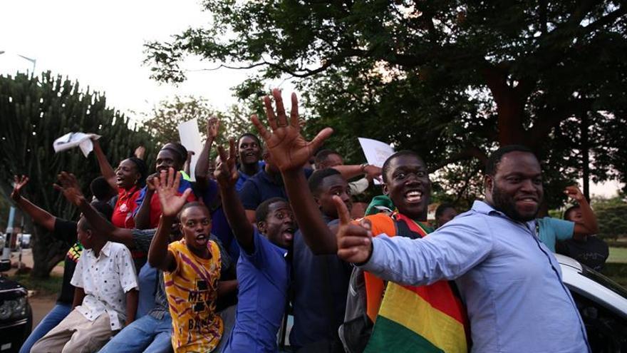 Un grupo de personas celebra la dimisión de Robert Mugabe como presidente en Harare (Zimbabue).