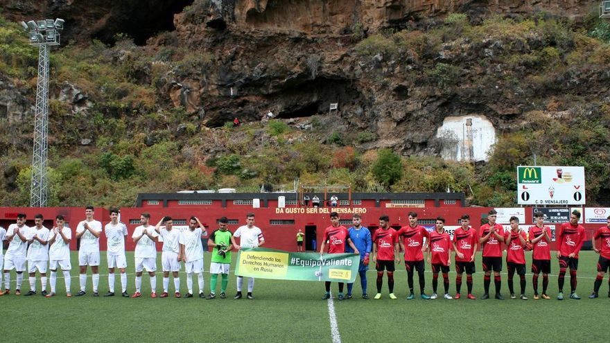 Los equipos CD Mensajero (d) y UD La Orotava con la pancarta.