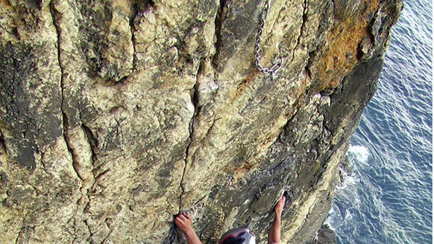 Escalador con casco visualiza bien los pies para colocarlos sobre roca firme en una vía junto al mar. Éstas suelen estar más erosionadas y los anclajes se deterioran antes.