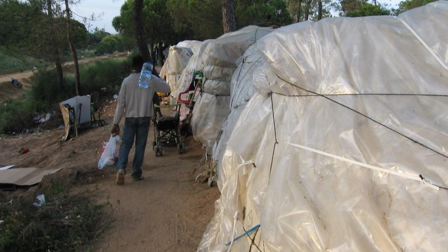 Un inmigrante porta agua en un campamento de chabolas en Lepe.