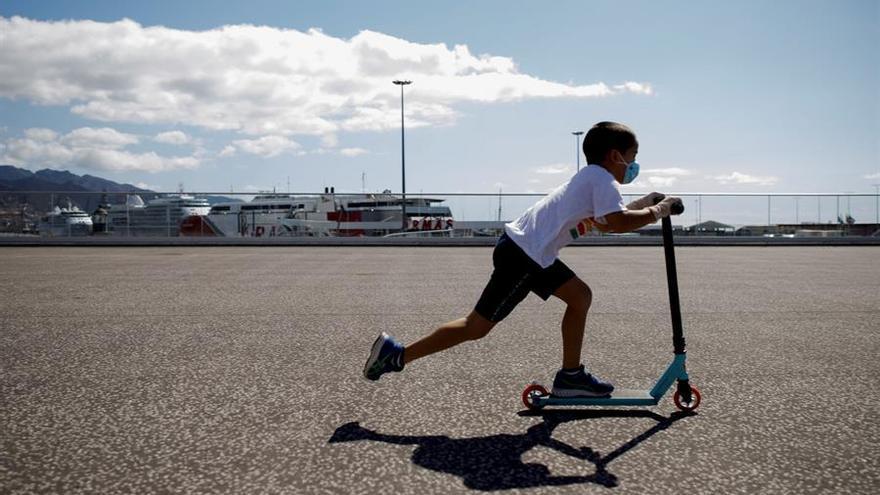 Un niño pasea con un patinete junto al puerto de Santa Cruz de Tenerife en este primer domingo en que pueden salir