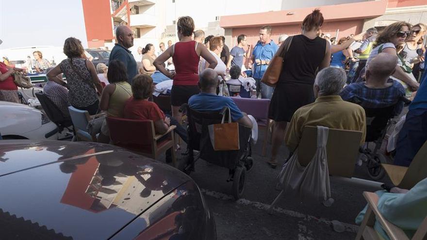 Familiares y personal médico de la residencia de ancianos de La Garita, junto a la que se declaró un incendio, atienden a los ancianos que fueron desalojados del inmueble momentaneamente y más tarde pudieron regresar a la instalación. (EFE/Ángel Medina G)