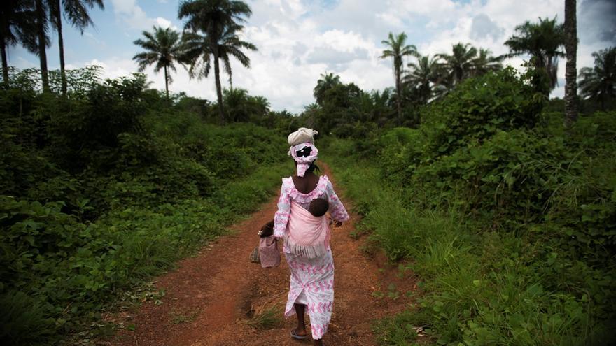 Muchas mujeres tienen que caminar kilómetros para llegar a un centro de salud. Sierra Leona, apenas cuenta con 300 médicos en todo el país para una población de casi 6 millones de personas. Una madre regreso a su aldea desde la clínica de Bumpe. Fotografía: Lynsey Addario/ VII