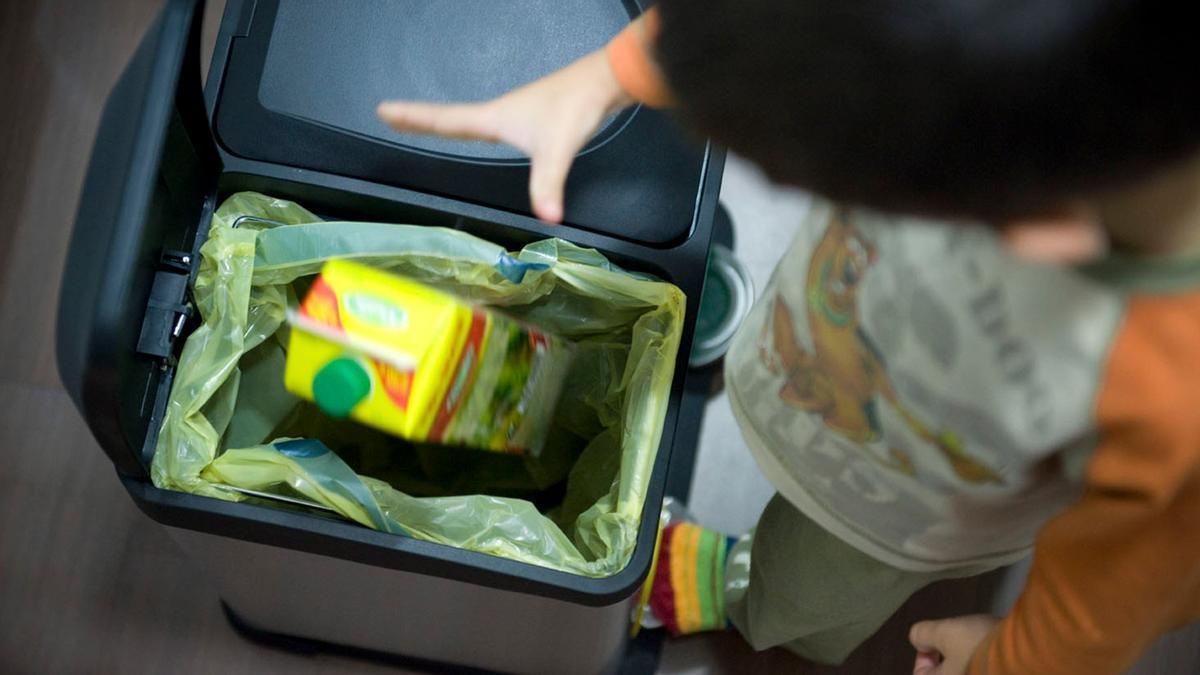Un niño reciclando un brik en el cubo amarillo
