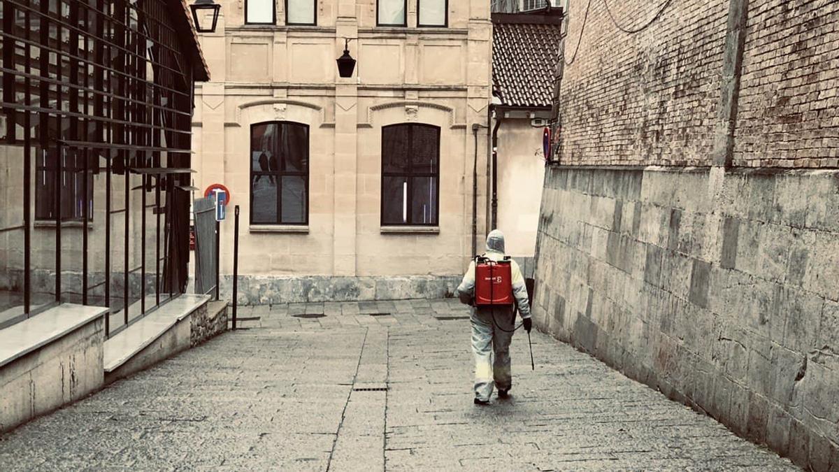 Un operario de limpieza desinfecta una calle vacía del centro de Vitoria en fin de año