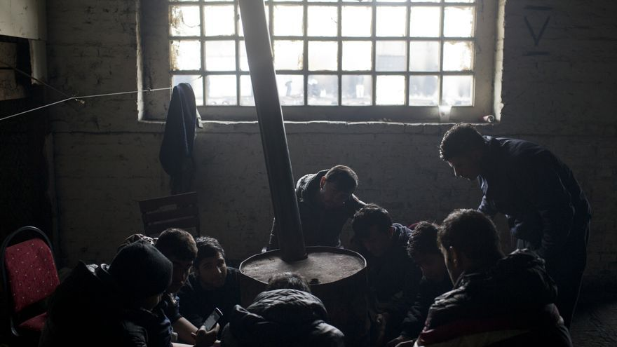 Refugiados de Afganistán se calientan con un viejo tambor de petróleo dentro de un almacén abandonado en Belgrado, Serbia, el jueves 5 de enero de 2017. | Foto: Marko Drobnjakovic / MSF