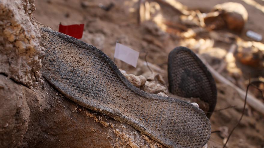 Suelas de zapatos, y numerosos objetos personales, emergen de la tierra. / JUAN MIGUEL BAQUERO