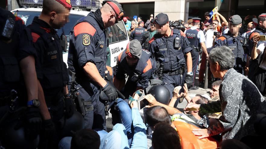 Los mossos retiran a los manifestantes sentados en la calzada ante la Conselleria de Exteriores de la Generalitat en Via Laietana el 20 de septiembre de 2017 al terminar los guardias civiles el registro.