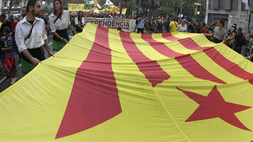 """Varias personas sostienen una bandera """"estelada"""" durante una manifestación de la Diada Nacional de Catalunya."""