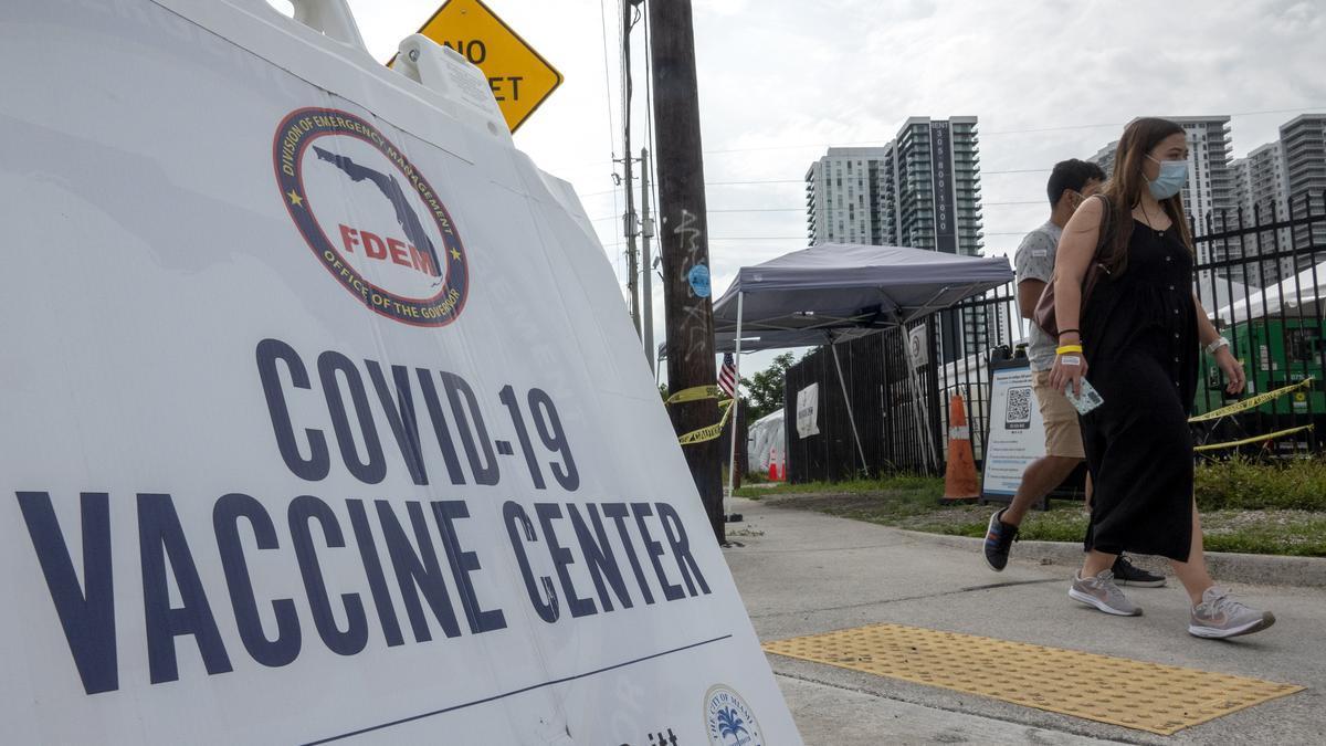Varias personas caminan cerca de un centro de vacunación sin cita previa contra la COVID-19 en Overtown, Miami.