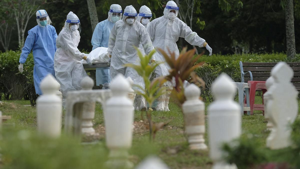 Personal de una morgue lleva los restos de una víctima de COVID-19 en cementerio de Malasia.