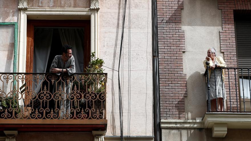 Dos vecinos conversan en el balcón de sus casas en Madrid durante la cuarentena por el coronavirus.