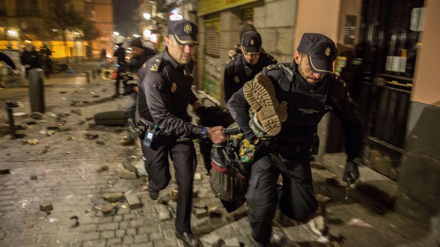 Agentes de la Policía Nacional trasladan a un senegalés herido de un porrazo en Lavapiés (Olmo Calvo)