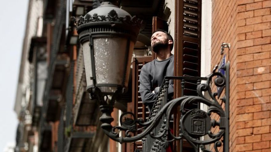 Un hombre asomado a su balcón.