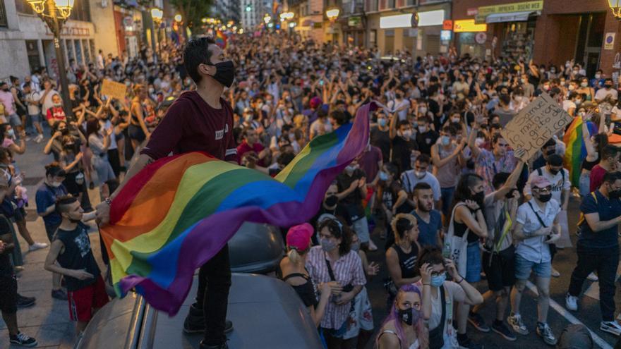 Un hombre ondea una bandera LGTBI ante una multitud que protesta contra la LGTBIfobia por las calles de Madrid.
