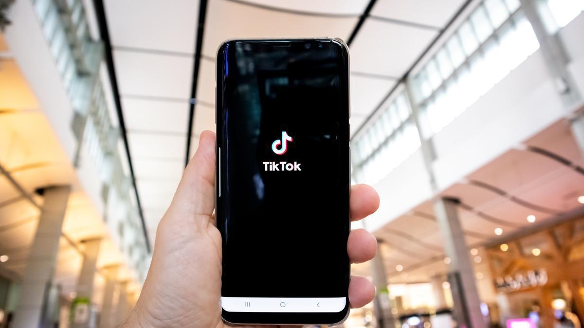 Una persona muestra la app de TikTok en un centro comercial.