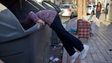 Una mujer, buscando en el interior de un contenedor en Sevilla