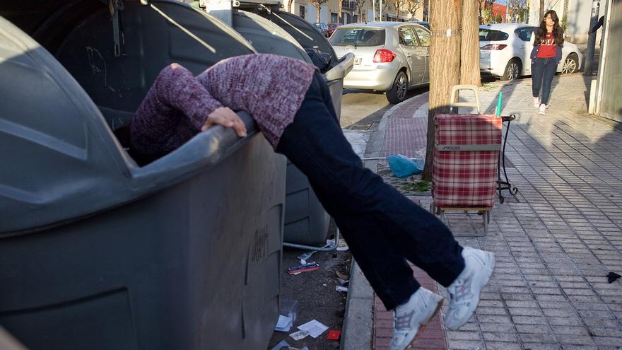 Imagen de archivo de una mujer buscando en un contenedor de basura.