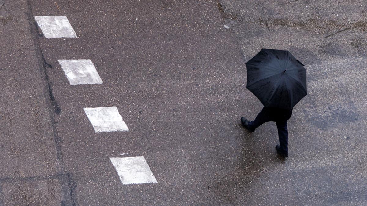 Una persona se protege de la lluvia con un paraguas . EFE/ Cati Cladera/Archivo