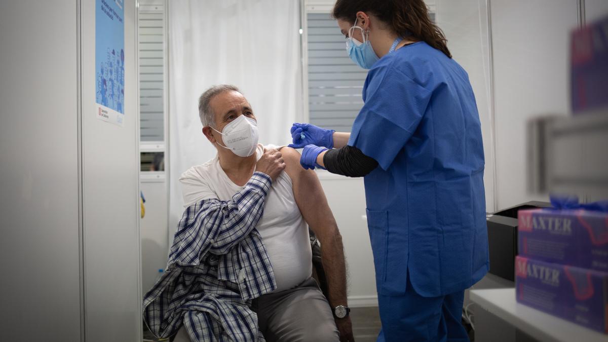 Una sanitaria vacuna a un hombre en el circuito de vacunación