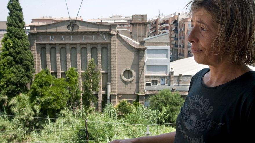 Assun Carreter, vecina de la fábrica que la empresa Uralita tenía entre las localidades de Cerdanyola y Ripollet (Barcelona), empresa condenada a indemnizar a los vecinos por los daños derivados de la exposición al polvo de amianto generado por la fábrica (al fondo).