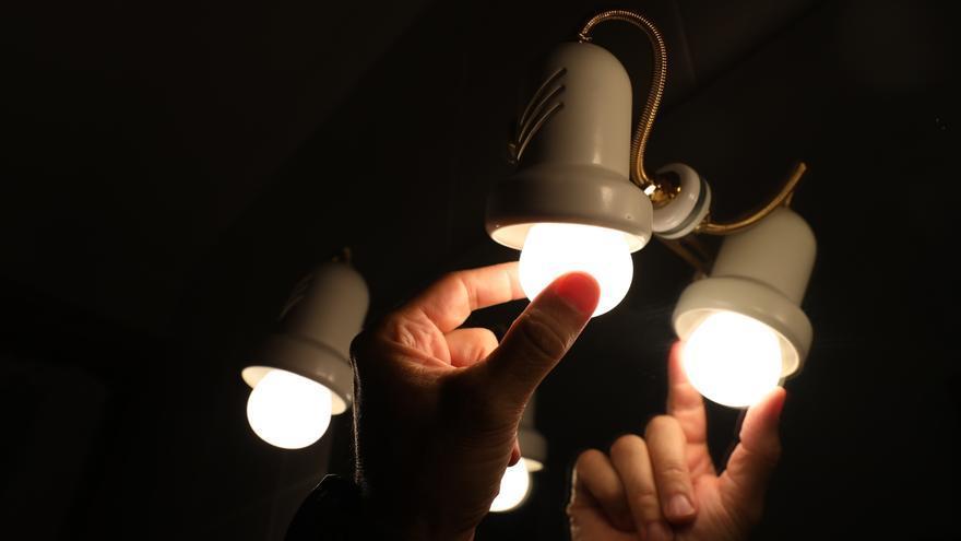 Una persona cambia la bombilla de una lámpara