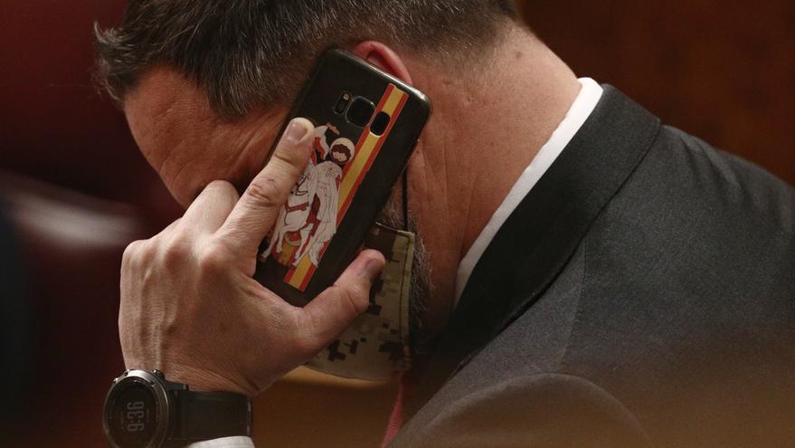El líder de Vox, Santiago Abascal, habla por teléfono durante una sesión plenaria