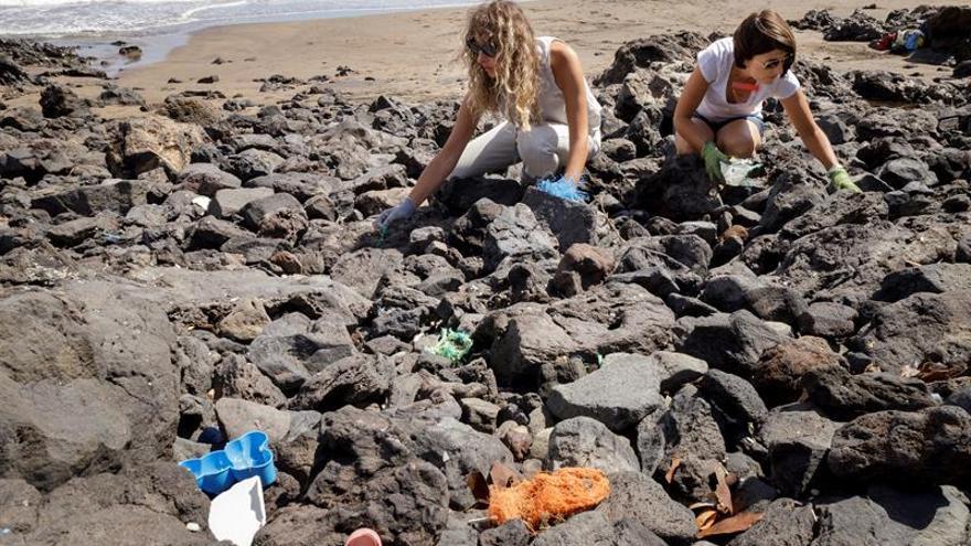 Magali Brincat (d) y Lucilla Bellini (i) realizan collares, pendientes, broches y pulseras con el plástico que encuentran en el mar que baña Tenerife
