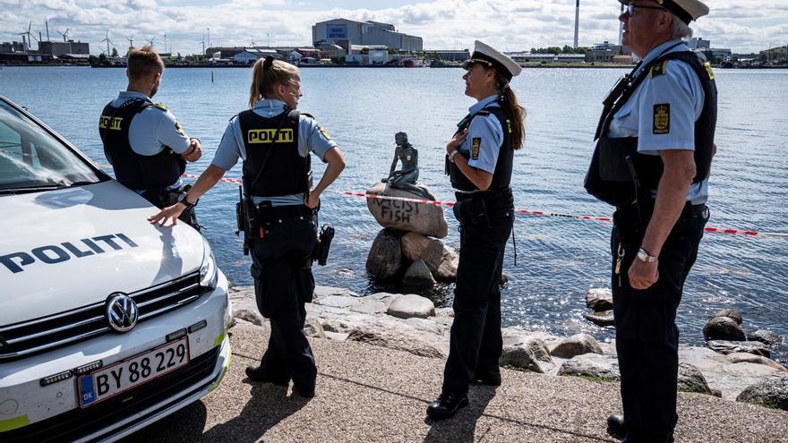La policía observa la pintada que reza 'Racist Fish' en la base del monumento nacional de La Sirenita en Copenhague, Dinamarca este viernes.