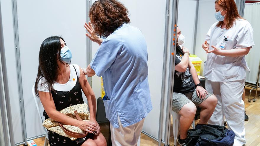 Dos personas reciben la primera dosis de la vacuna de Pfizer